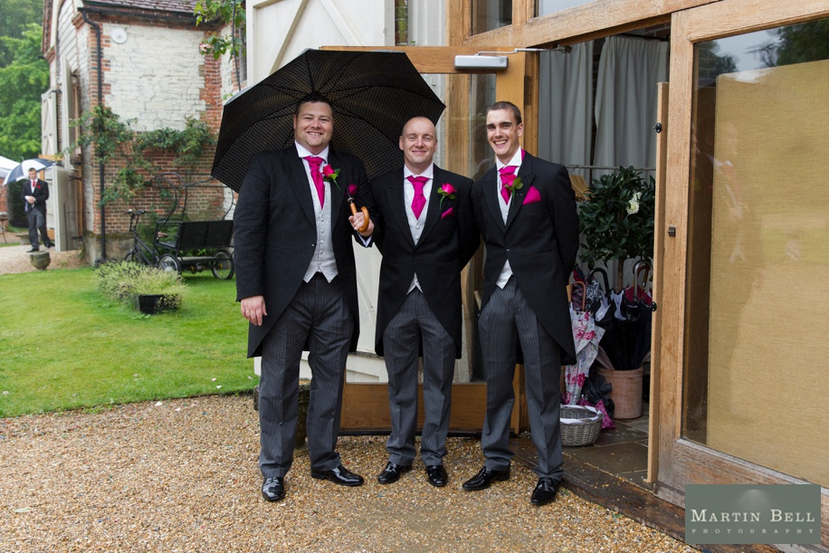 Groomsmen with morning suits and a pink colour scheme