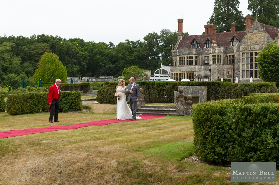 Bride walking down the aisle at a Rhinefield House wedding - Outdoor ceremony