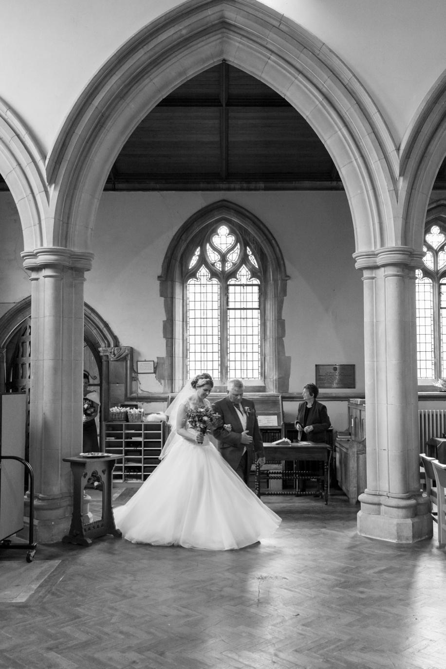 Wedding photographer Hampshire - St Thomas All Saints Church, Lyminton wedding - Bride walking down the aisle