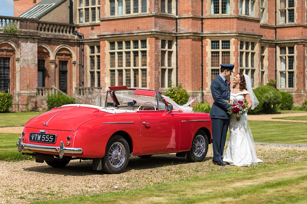 An RAF military wedding in Hampshire by award winning wedding photographer Martin Bell Photography - Red vintage wedding car