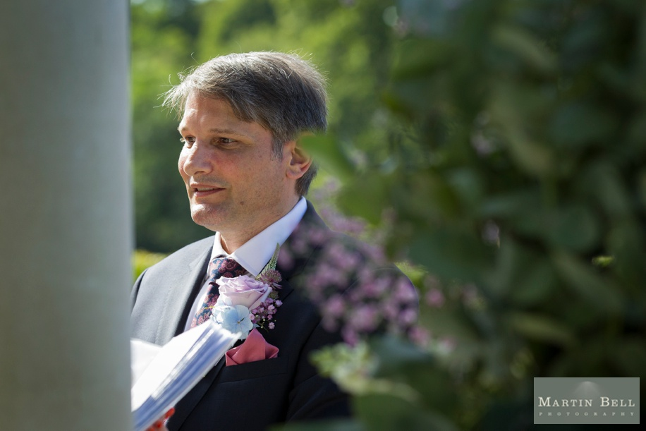 Groom's reaction to Bride walking down the aisle - small outdoor wedding ceremony at Rhinefield House