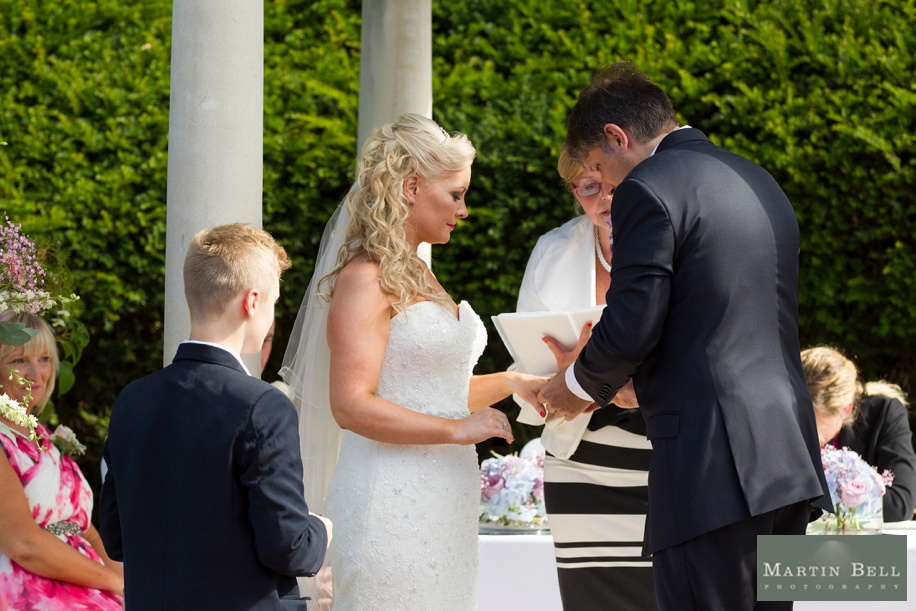 Bride and Groom exchanging wedding vows in an outdoor ceremony at Rhinefield House