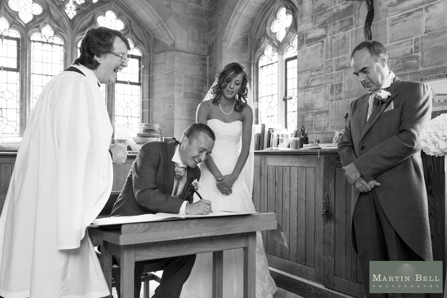 Wedding ceremony vows at St Nicholas church in Brockenhurst - Fun signing the register photograph