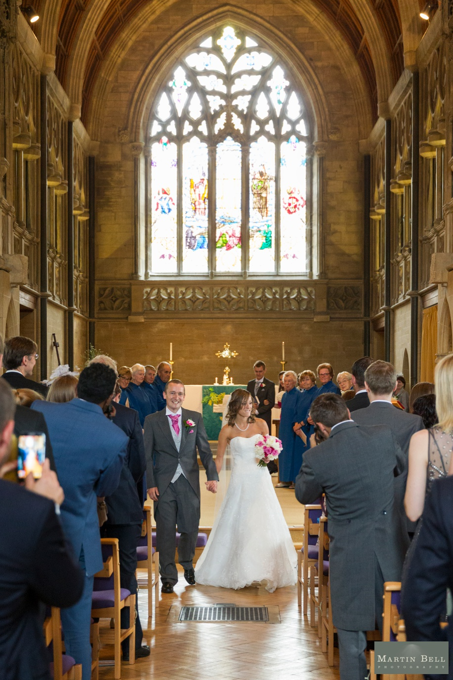 Wedding ceremony vows at St Nicholas church in Brockenhurst - Bride and Groom walking up the aisle