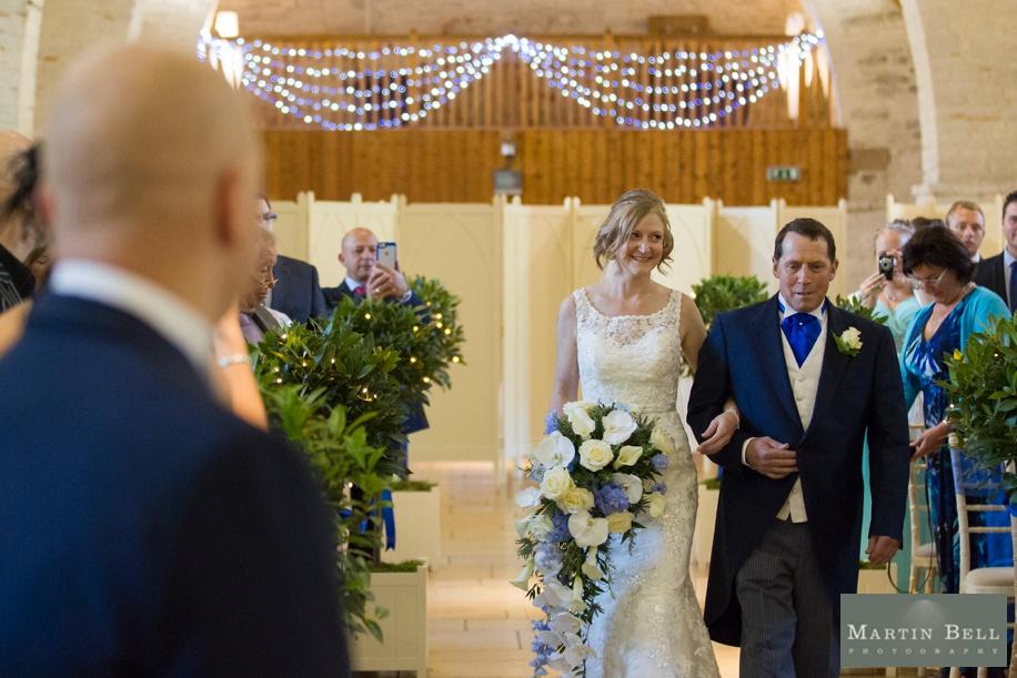 Bride walking down the aisle at a Tithe Barn wedding